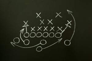 Game strategy drawn with white chalk on a blackboard.